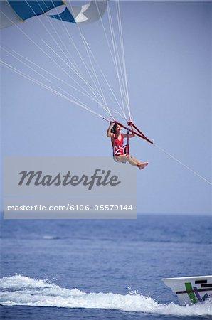 Woman parascending behind motorboat