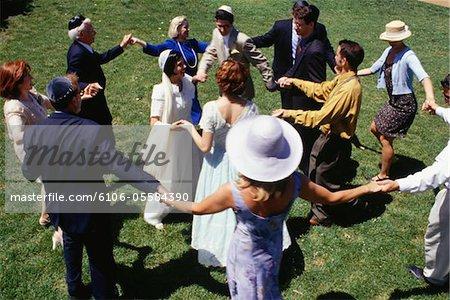 Bride, groom and guests dancing at wedding in garden