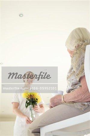 Carer brings an elderly woman a vase of flowers