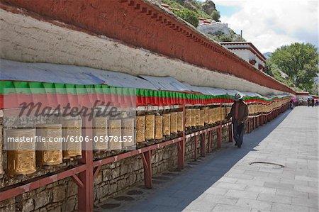Pilgrim Spinning Prayer Wheels at Potala Palace