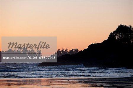 Man standing on seaside cliff watching sunset