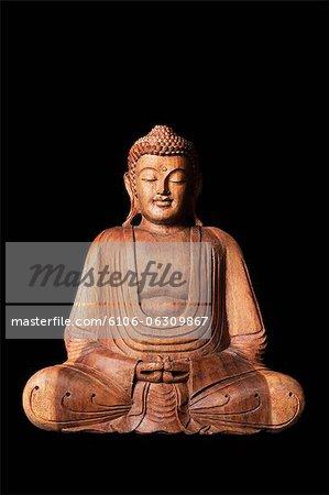 Statue of wooden Buddha sitting.