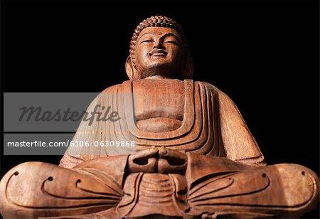 Closeup of sitting wooden Buddha statue.