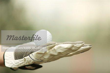 Gloved hand holding golf ball,close-up