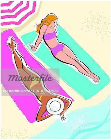 Two women lying on beach