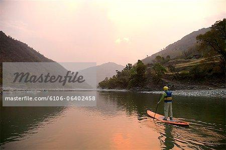 Man paddling iSUP down river at sunset.