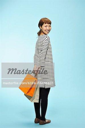 Young woman carrying shopping bags , smiling