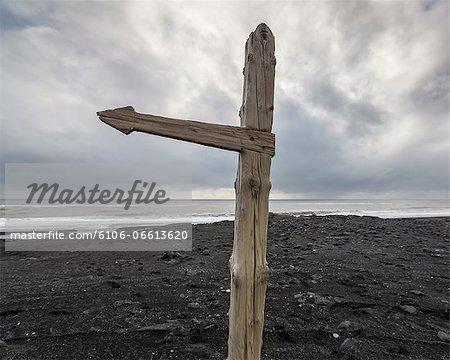 Directional post on black sand beach