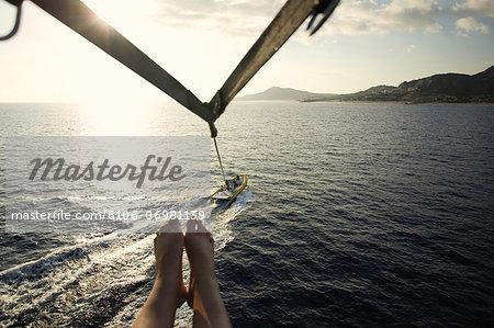 Mexico, Baja, Cabo San Lucas, mature woman parasailing, low section