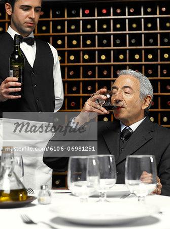 Senior businessman tasting wine, waiter holding bottle
