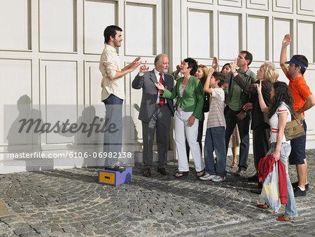 Man standing on box in street speaking to crowd raising hands