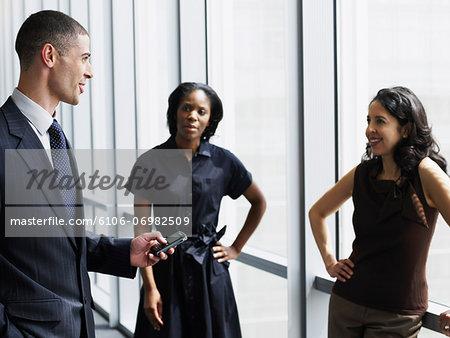Three business executives meeting in hallway, man using PDA