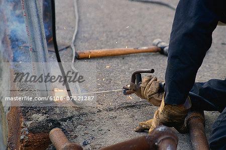 Worker welding steel pole