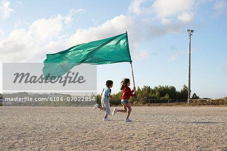 Children (9-12) running on beach with flag