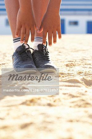 Boy (12-13) doing gymnastics on sand, low section