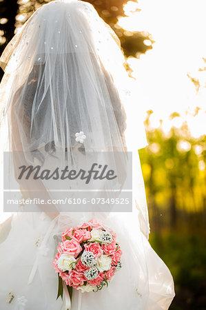 bride in veil holding flowers outdoor