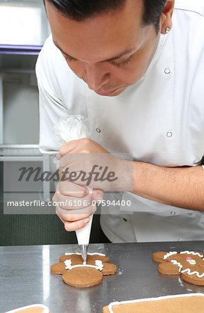 Artisan baker decorating gingerbread man