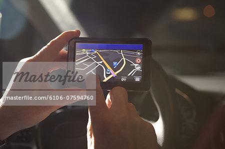 man using gps sat nav at night in car