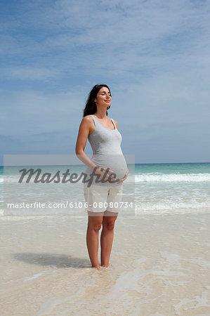 Happy pregnant woman on beach