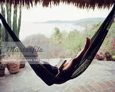 woman reads in hammock overlooking ocean