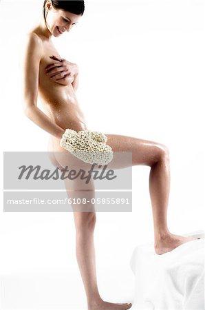 Naked woman using a massage glove (studio)