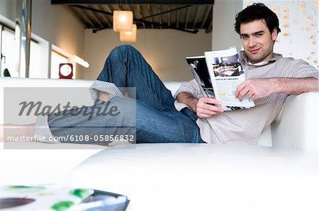 Man lying on a sofa, reading magazine