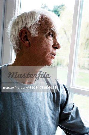 Thinking senior man looking through a window