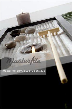 Candles, peebles and rake in zen garden, close-up