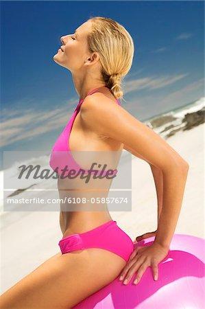 Young woman in pink bikini on the beach, sitting on a large ball