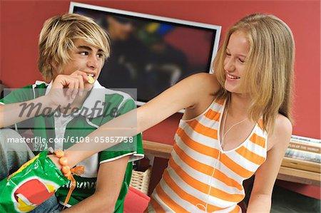 Teenage boy and girl eating crisps
