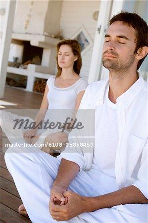 Young couple in yoga attitude, outdoors