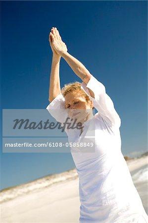 Senior woman doing yoga on the beach