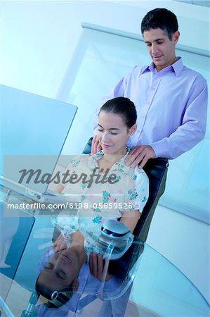 Businessman massaging businesswoman, smiling