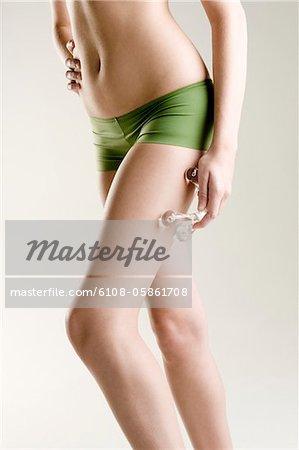 Woman massaging her leg with a massager