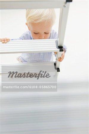 Baby boy climbing a step ladder