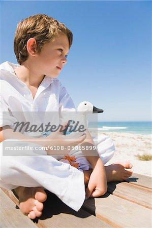 Boy sitting on a boardwalk and holding a toy bird