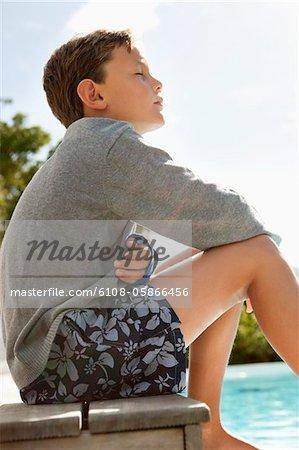 Boy day dreaming near a swimming pool
