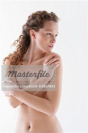 Naked woman hugging herself
