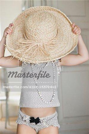 Cute little girl wearing oversized straw hat