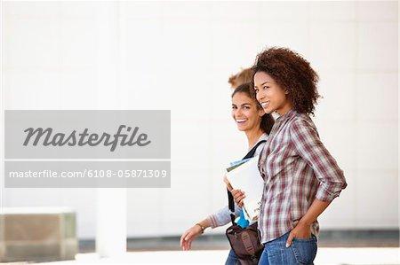Two female friends walking in campus
