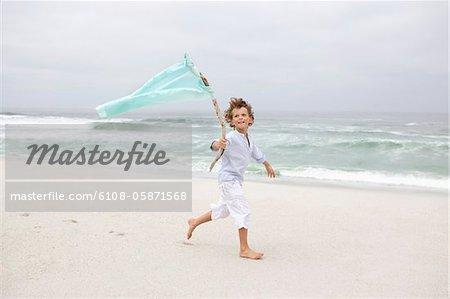 Boy running while holding flag on beach