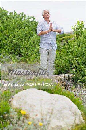 Senior man meditating in a garden