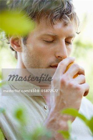 Close-up of a man smelling a lemon