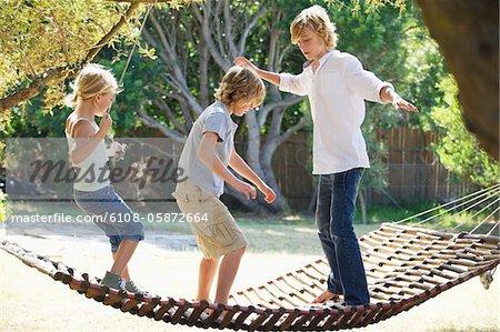 Little siblings standing in hammock