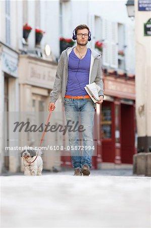 Man holding a dog on leash, Paris, Ile-de-France, France