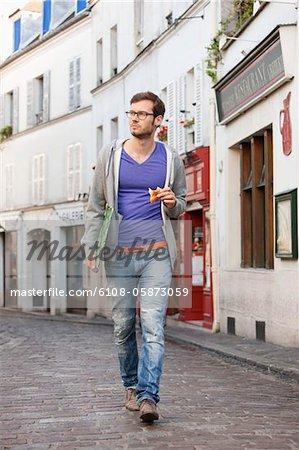 Man carrying a file while eating food, Paris, Ile-de-France, France