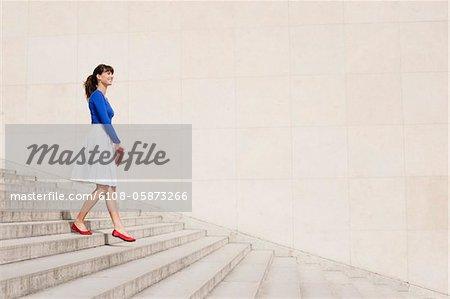 Woman moving down steps, Paris, Ile-de-France, France