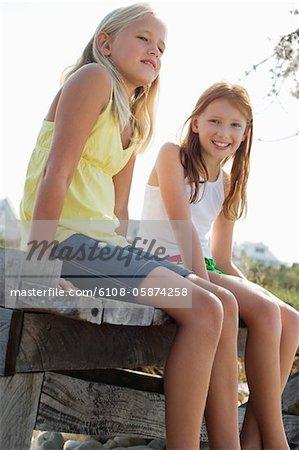 Two girls sitting on a boardwalk