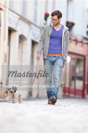 Man holding a dog on leash walking on the street, Paris, Ile-de-France, France