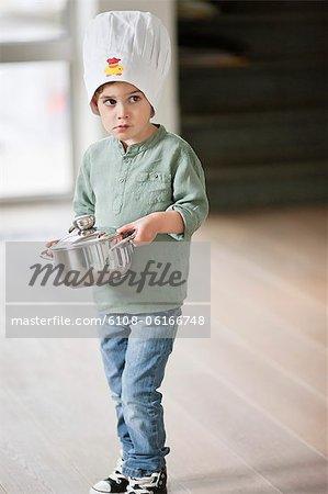 Boy carrying a saucepan